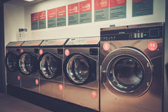 Laundry machines at laundromat shop. Royalty Free Stock Photos