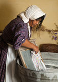 Laundry maid. Victorian woman washing laundry with an antique washboard Stock Photo