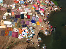 Laundry Map. A birds eye view of lots of poor people from Indian washing clothes and drying them on the banks of a river. The whole scene appears like a Stock Images