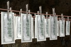Laundry money drying. 3D render of one hundred dollar banknotes hanging on laundry line attached with wooden clothes pegs against dark brown wall Stock Images