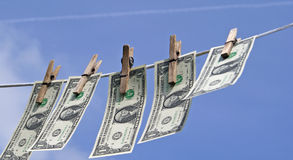 Laundry money. One dollar bills on laundry line attached with wooden clips over blue sky Royalty Free Stock Photos