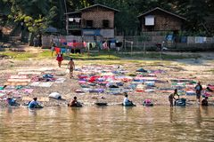 Laundry in Myanmar. MINGUN, MYANMAR - NOVEMBER 25: People from Mingun washing and drying clothes in the traditional way on the 25th of November 2018 in Myanmar stock images