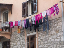 Laundry over washing line. Fresh washed clothes hanging over a washing line. Mainly pink clothes royalty free stock photos