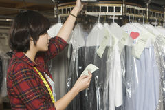 Laundry Owner Reading Receipt By Clothes Rail. Female owner reading receipt by clothes rail in laundry royalty free stock photos