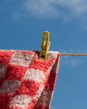 Laundry pin holding woolen cloth. Clothes peg holding red fleecy blanket against the blue sky Royalty Free Stock Photos