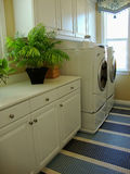 Laundry Room. With a washer and dryer and lots of storage cabinets blue and white rug, a window with a blue and white valance Stock Images
