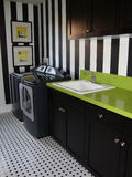 Laundry Room. With black appliances and black cabinets green counter tops and black and white stripped wall paper and a sink Royalty Free Stock Photos