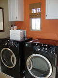 Laundry Room. With black appliances washer and dryer and white cabinets Stock Photo