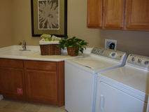 Laundry Room. Large laundry room with washer and dryer and cabinets with a sink stock photography