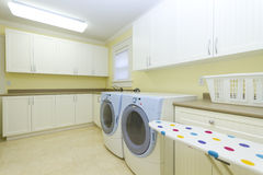 Laundry room. With a sink and a washer, dryer, ironing board Royalty Free Stock Image