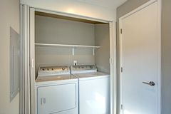 Laundry room hidden behind white folding doors. Laundry room hidden behind white folding closet doors with white washer and dryer stock photography