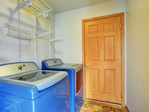 Laundry room interior with blue washer and dryer. Also shelves Stock Photo