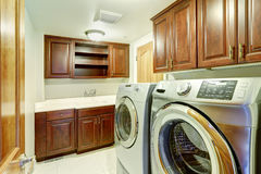Laundry room interior with modern steel appliances Stock Photography