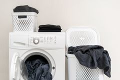 Laundry room interior with washing machine near wall. Ready for laundry process. White washing machine with soft blanket inside standing near basket of clothes royalty free stock photos