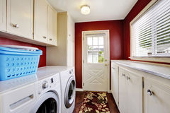 Laundry room interior with white cabinets and red walls. Stock Photos