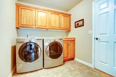 Laundry room with modern appliances. And light tone cabinets Royalty Free Stock Photo
