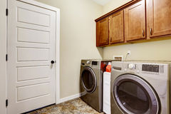 Laundry room with steel appliances and nice cabinets Royalty Free Stock Photo