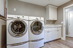 Laundry room with taupe walls and modern appliances. Laundry room with taupe walls, white cabinets and marble top counters royalty free stock photos