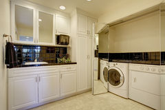 Laundry room with washer dryer, and miror folding doors. Royalty Free Stock Photos