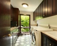 Laundry room with wood cabinets and white washer and dryer. stock photo