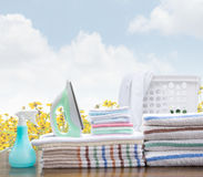 Laundry Service. Stack Of Towels And Utiliies For Laundry Service Concept With Sky And Flower Background Stock Photo