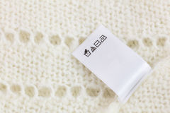 Laundry tag on white knitted wool sweater background Royalty Free Stock Images