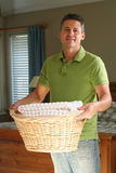 Laundry time. Attractive man holding a basket of clean laundry Stock Photos