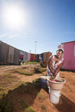 Laundry time. An image of an african woman doing her laundry in the township with only a single bucket of water smiling brightly Royalty Free Stock Photos