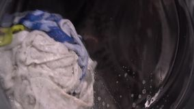 Laundry washing in a front load washing machine. Laundry washing in a front loading washing machine viewed spinning around in the soapy water through the door stock footage