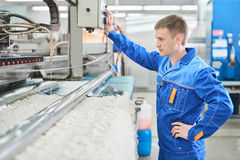 Laundry worker in the process of working on automatic machine for carpet washing. In dry cleaning royalty free stock photos
