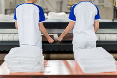 Laundry worker puts ironed textile Stock Images