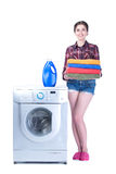 Laundry. Young beautiful woman doing laundry in the washing machine. Isolated on white background Stock Photos
