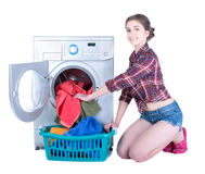 Laundry. Young beautiful woman doing laundry in the washing machine. Isolated on white background Royalty Free Stock Photos