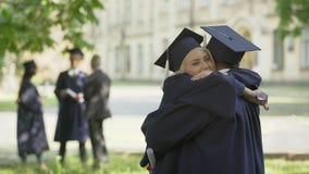Laureati che hanno conversazione, abbracciantesi, amicizia dell'università archivi video