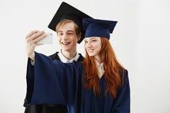 Laureati degli amici dell'istituto universitario in cappucci che sorridono facendo selfie sopra fondo bianco Fotografie Stock