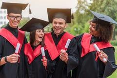 Laureati emozionanti che presentano i loro certificati di istruzione superiore Immagini Stock Libere da Diritti