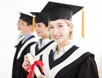 Laureato alla graduazione con i compagni di classe Immagini Stock