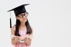 Laureato asiatico felice del bambino della scuola in cappuccio di graduazione Immagini Stock