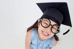 Laureato asiatico felice del bambino della scuola in cappuccio di graduazione Fotografia Stock