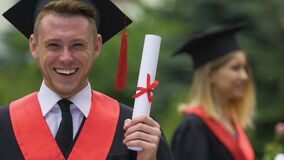Laureato del maschio in diploma accademico dell'università della tenuta del vestito, sorridente alla macchina fotografica stock footage