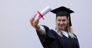 Laureato felice che mostra il suo nuovo diploma di graduazione video d archivio