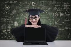 Laureato felice della femmina con un computer portatile Immagini Stock Libere da Diritti