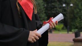Laureato piacevole della femmina in diploma accademico della tenuta del vestito, futuro luminoso archivi video