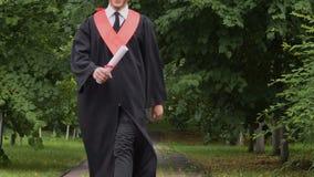 Laureato sorridente felice che cammina nel parco con il diploma, saltante con l'eccitazione video d archivio
