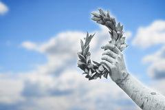 Laurel Wreath hand held by a bronze statue. On sky background whit copy space Stock Images