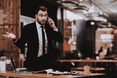 Laut sprechen am Telefon Klage eines Mannes arbeitsplatz lizenzfreie stockbilder