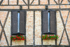 Lautrec (France), old village. Lautrec (Tarn, Midi-Pyrenees, France), medieval village with half-timbered buildings: two windows with flowers Stock Image