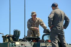 LAV crew members at open day. GREYMOUTH, NEW ZEALAND, NOVEMBER 18, 2017: Crew members of a Light Armoured Vehicle LAV discuss matters at an open day for the Royalty Free Stock Images