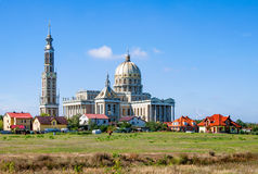 lav poland Extremt stor kyrka i en liten by Arkivbilder