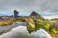 Lava beach, Western Iceland. Low tide scenery at the Djupalonssandur beach at the foot of the Snefellsjokull volcano in Iceland. Surreal landscapes with craggy royalty free stock photography